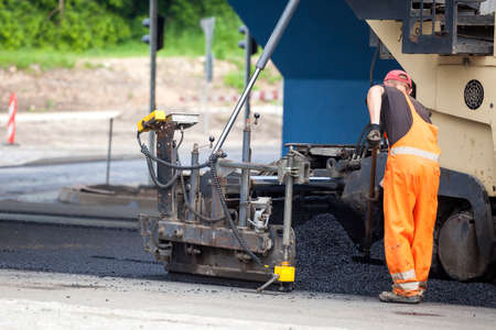 workers and the asphalting machines