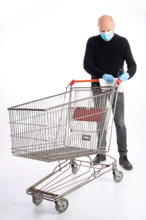 Man with mouth protection and hand gloves cleaning a shopping cart, isolated on white background