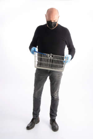 Man with mouth protection and hand gloves looking in his shopping basket, isolated on white background