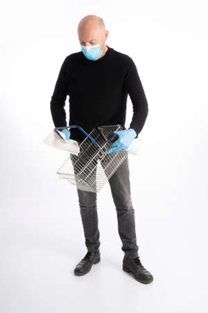 Man with mouth protection and hand gloves cleaning a shopping basket, isolated on white background