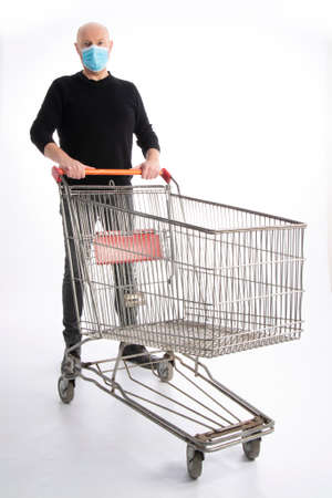 Man with mouth protection pushing a shopping cart, isolated on white background