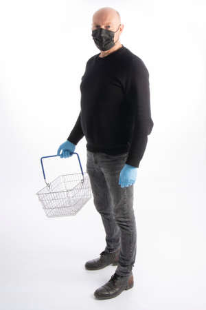 Man with mouth protection and hand gloves carrying a shopping basket, isolated on white background
