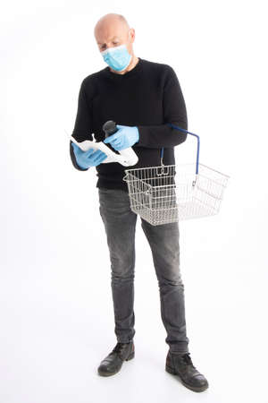 Man with mouth protection and hand gloves starting to clean a shopping cart, isolated on white background