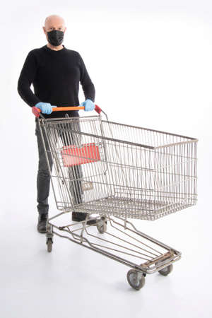 Man with mouth protection and hand gloves pushing a shopping cart, isolated on white background