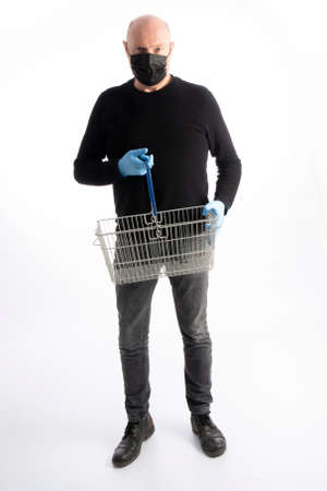 Man with mouth protection and hand gloves holding a shopping basket, isolated on white background