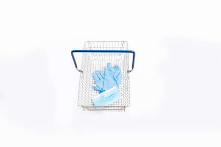 Shopping basket with hand gloves and mouth mask, isolated on white background Stock fotó