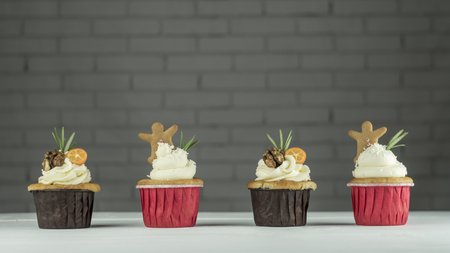 Four Christmas cupcakes with kumquat, walnuts and ginger cookies on the table
