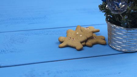 Gingerbread and Christmas tree on blue table Фото со стока