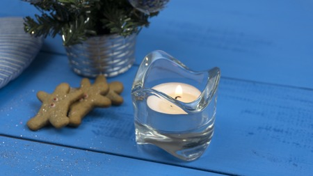 Christmas decorations on a blue table: cookies, candle, christmas tree
