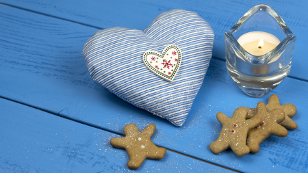 Christmas decorations on a blue table: cookies, candle, heart toy