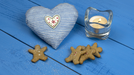 Christmas decorations on a blue table: cookies, gingerbread, heart toy