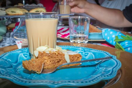 Colorful Tea party with pumpkin quiche ready to be eaten on a blue plate with fork and a cup of coffee in glass cup