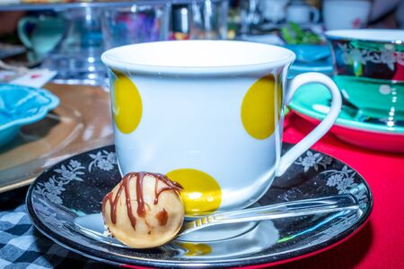 Colorful Tea party with cup of tea in a yellow spotted tea cup and sweet chocolate treat on a tea saucer and a silver tea spoon