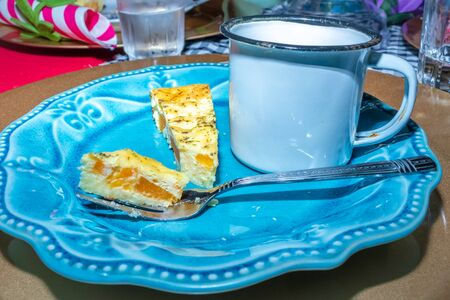 Colorful Tea party with pumpkin quiche ready to be eaten on a blue plate with fork and a cup of coffee in a tin cup