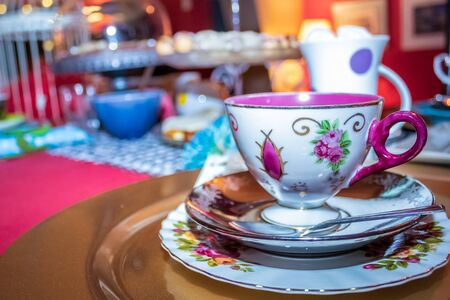 Colorful party with table laid out fancy teacups, cutlery and crockery, sweet and savory food.