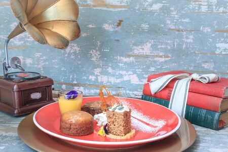 Chocolate brownie, malva pudding, pumpkin spice cake with glazed frosting and lemon curd in a small glass on a colorful plate with icing sugar decoration, old grammar phone and antique books 免版税图像