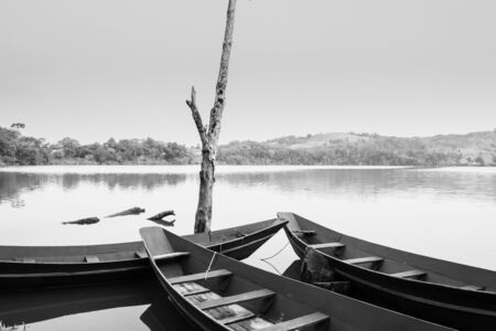 View of a wooden boats and big dry tree growing on Lake Nyabikere, with and the reflections on the water at sunrise, Rweteera, Fort Portal, Uganda, Africa Banque d'images