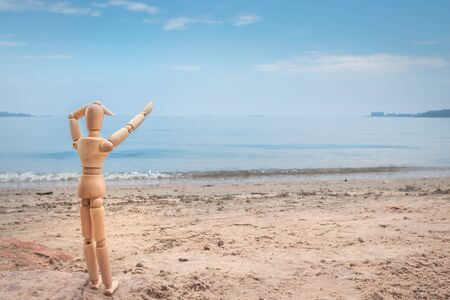 Little wooden manikin looking out towards Lake Victoria from the golden sandy shore line, Entebbe, Uganda, Africa Stock Photo