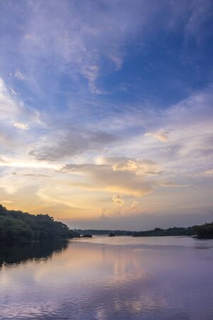 Sunset view of the Victoria Nile river, with trees growing and the reflections on the water, Jinja, Uganda, Africa