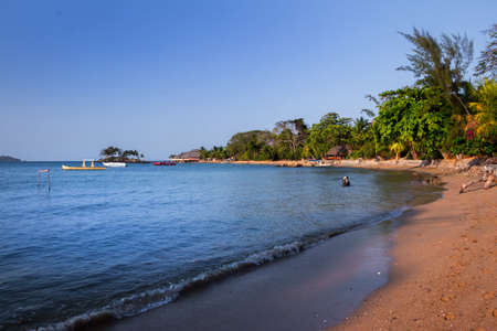 View of coastline on Nosy Komba Island lined with palm trees and beautiful sandy beaches, Madagascar