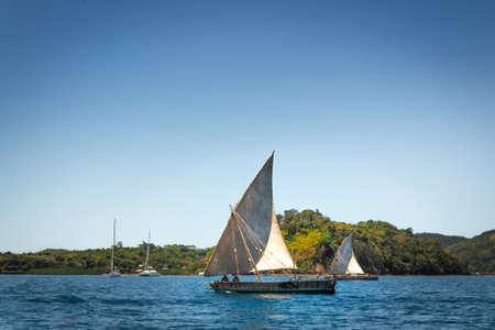 View of Nosy Komba Island coastline with a sail boat sailing on the sea, Nosy Komba, Madagascar
