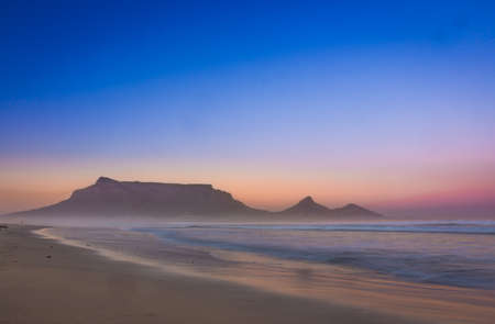 View of Table Mountain at sunrise, Cape Town, South Africa from Milnerton Beach coastline Banco de Imagens