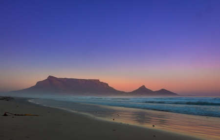 View of Table Mountain at sunrise, Cape Town, South Africa from Milnerton Beach coastline