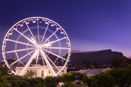 View of Table Mountain and a big white Ferris wheel located at the waterfront at sunset on a beautiful calm evening, Cape Town, South Africa