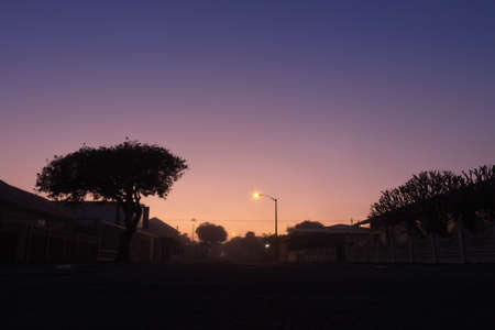 Road running through suburban neighborhood houses at sunrise on a misty morning, Cape Town, South Africa