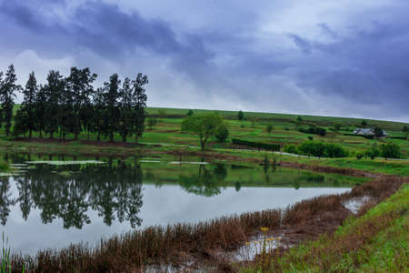 A Country side with a Gravel Road bends around an almost still lake with tree reflections on it, surrounded by beautiful green hills and a stormy sky.