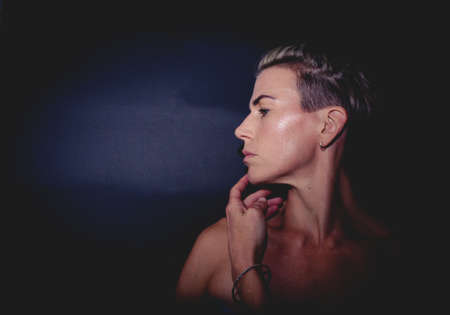 Portrait of a muscular, blonde short haired Caucasian woman in the dark