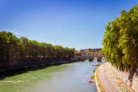 View of the Tiber river in Rome City with bridge crossing the river lined with green trees, Rome, Italy, Europe