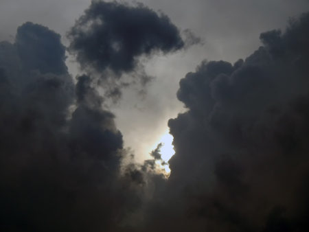 emergence: The emergence of the sun from the clouds in the sky close-up