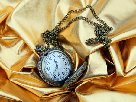 Old clock on gold satin material closeup