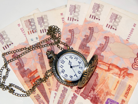 Antique clock with a chain on the background of Russian money