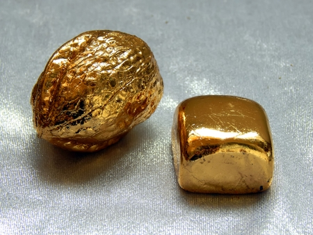 foil: Gold bar with walnut nuts on a silvery background