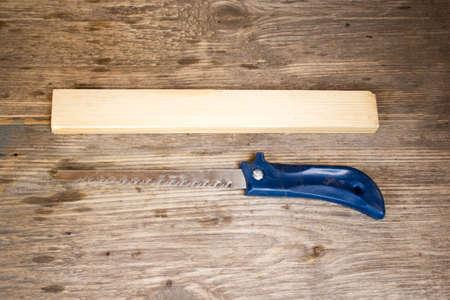 serrucho: sierra de mano sobre un fondo de tablas de madera con espacio para texto