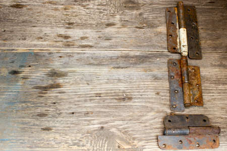 hinge joint: metal door hinge on a grungy wooden background,  Copy space to right.