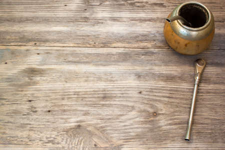 mate infusion: Calabash and bombilla with yerba mate on wooden background. Copy space to right.