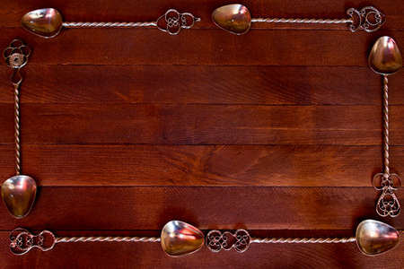 arranged: silver teaspoon arranged over dark wooden table, top view