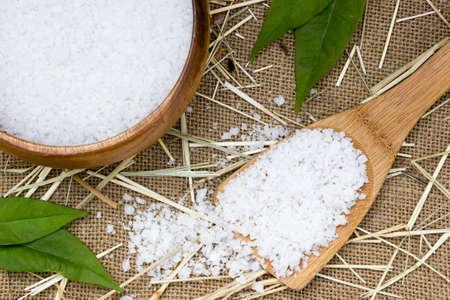 sediments: Sea salt in wooden spoon on burlap sack background Stock Photo