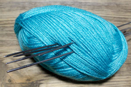 acrylic yarn: Skein fluffy blue yarn, metal spokes with  on wooden table