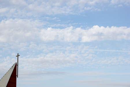 arrepentimiento: Cruz cristiana en steeple contra el cielo azul y las nubes
