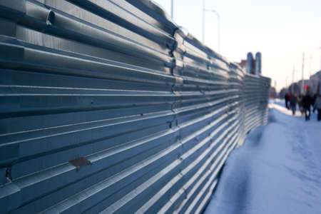 roof profile: Green metal fence along the winter road Stock Photo