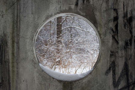 round window: A concrete wall with a round window in winter forest