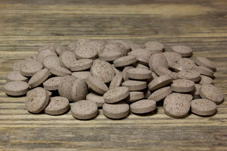 nutritional therapy: Herbal brown pills on wooden background.