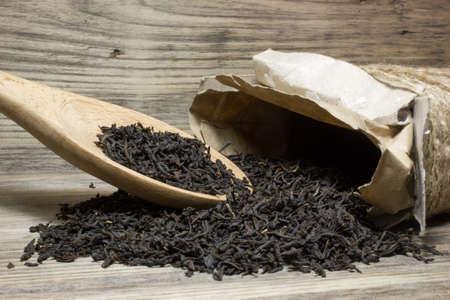 Trockene Teeblätter für schwarzen Tee und hölzernen Löffel auf Holzuntergrund
