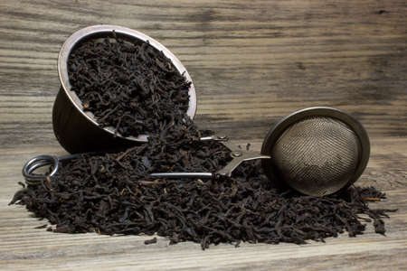 Dry tea leaves for black tea on wooden background Banco de Imagens - 52820317
