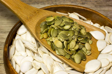 Pumpkin seeds and wooden spoon on wooden background Stock Photo