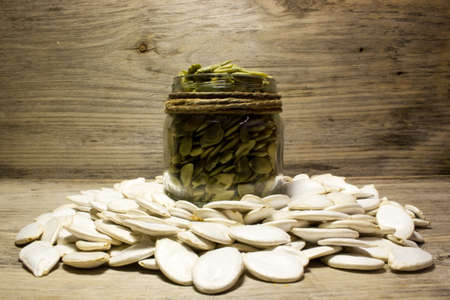 pumpkinseed: Pumpkin seeds and jar on wooden background Stock Photo